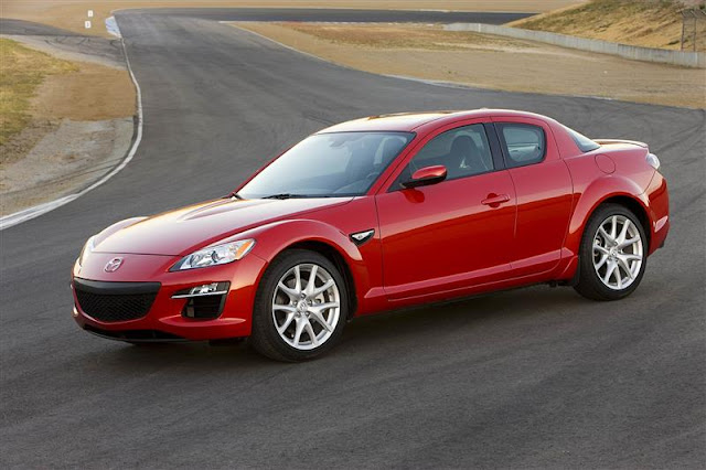 Front 3/4 view of red 2011 Mazda RX-8 parked on racetrack