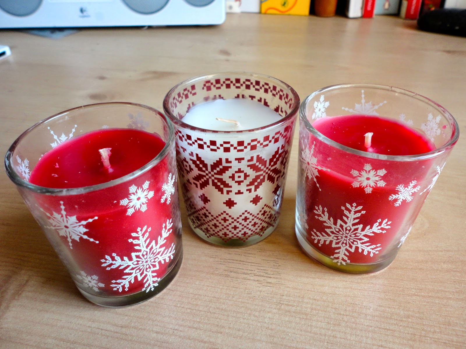 Red and white Christmas scented candles in glass holders