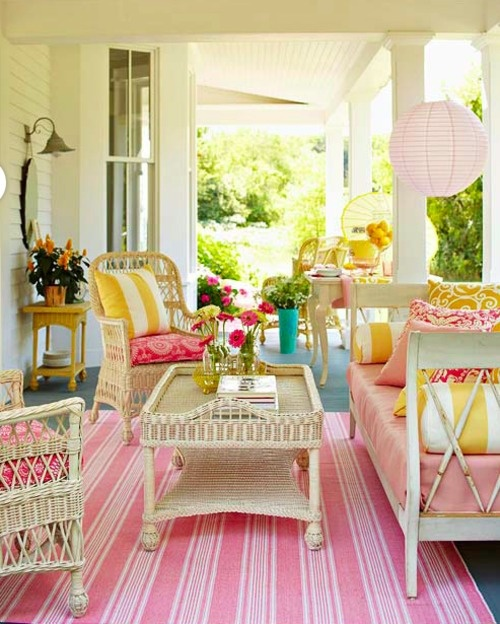 Pink, yellow, and green pops of color look fresh and exciting with white wicker furniture on this spring front porch