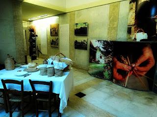 Interior do Monumento do Imigrante. Mesa com produtos de vime, painéis e fotos de imigrantes italianos.
