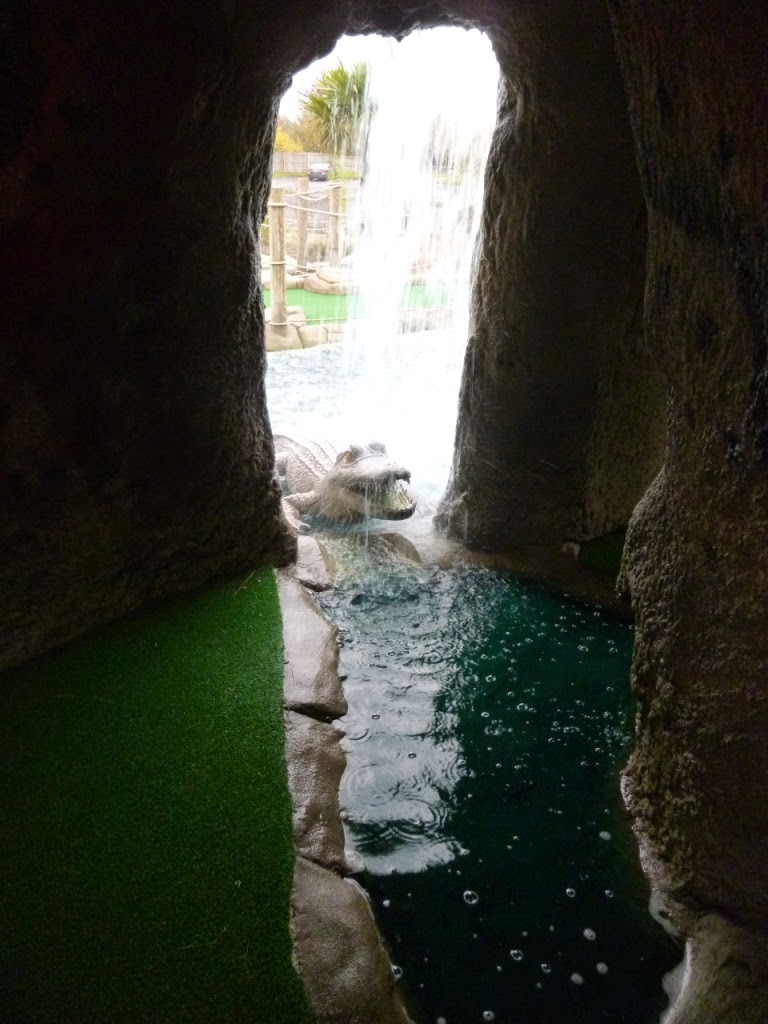 A croc emerges from the water at the Jungle Island Adventure Golf course at Horton Park Golf Club in Epsom, Surrey