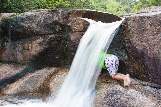 boy climbing behind a waterfall