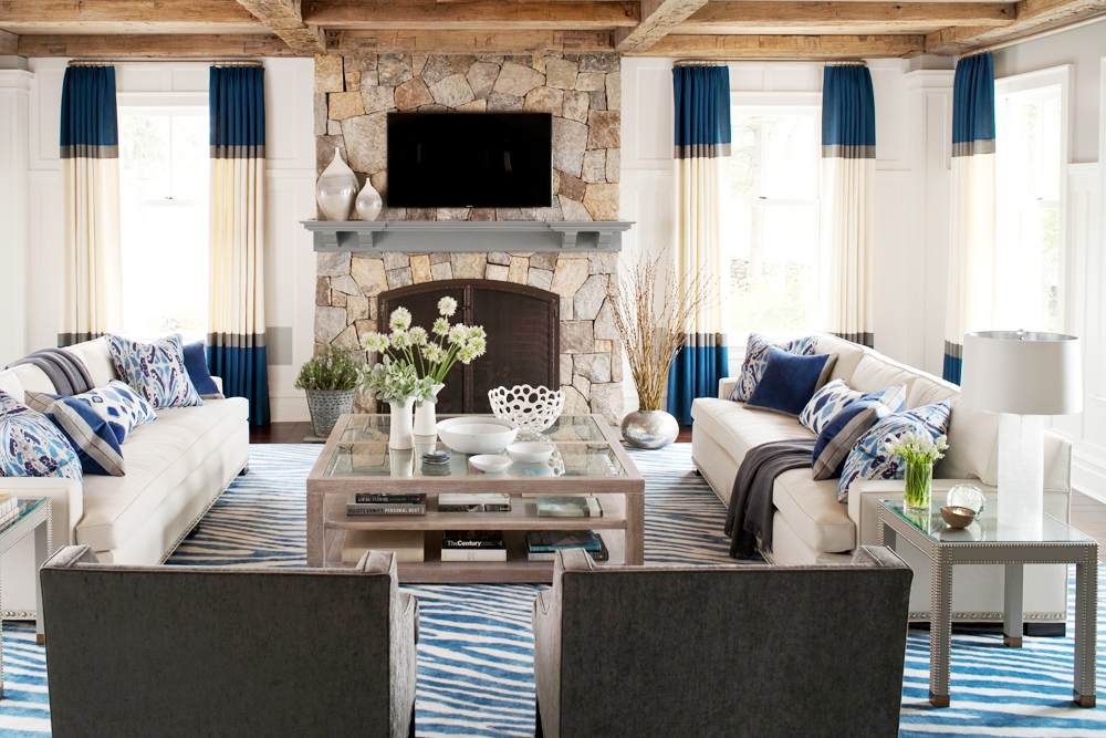 living room with color block curtains a stone fireplace dueling facing sofas exposed