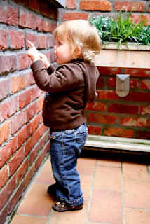 Chld looking at a brick wall
