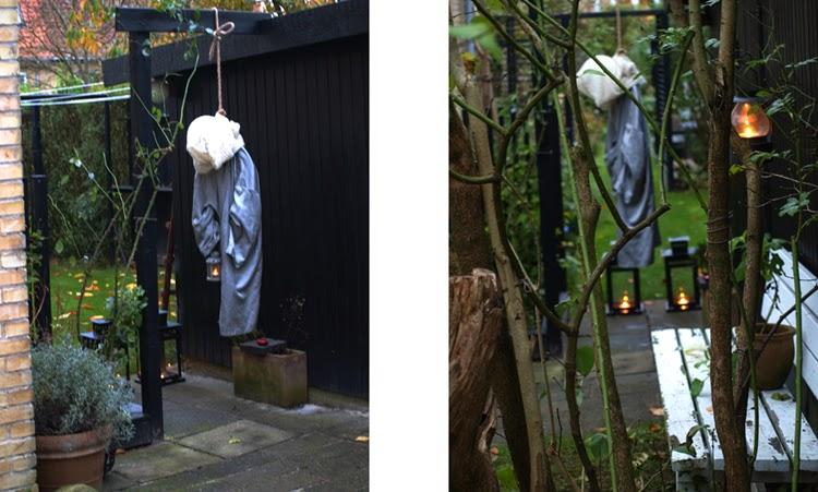 En hængt mand lavet af et skaft med ballon som hoved og arme af haveslange dingler som hængt mand i haven