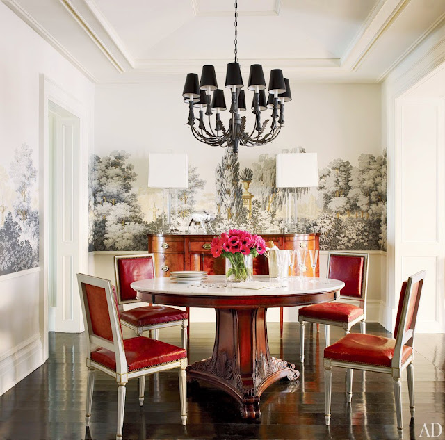 Zuber wallpaper mural in a breakfast nook with a round redwood table, red leather upholstered Louis XIV chairs and a black chanderlier
