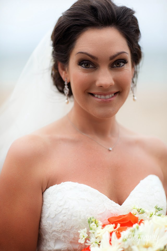 Bridal portraits on the beach, veil in wind, orange wedding flowers