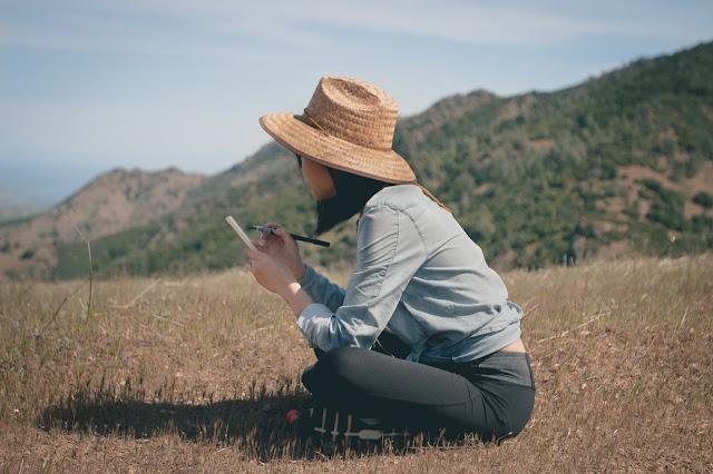 Fotografia por Nirzar Pangarkar que mostra uma mulher sentada no campo com um caderno em mãos. Ela parece estar anotando, criando conhecimento, categorizando a natureza ao seu redor. Em outras palavras, ela está promovendo generalizações.
