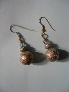 Bronze-color earrings with three beads. A pale blue small bead on top of a slightly cylindrical bronze bead with texture like vertical stripes, and a larger round bronze bead with designs imprinted on the metal.