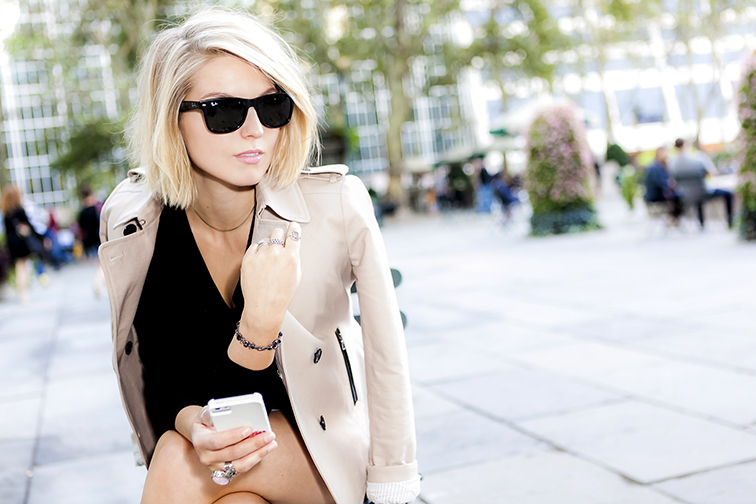 fashion over reason in Bryant Park, on the phone, Ray-Ban Wayfarers, Saint Laurent arty ring, NARS Roman Holiday lipstick