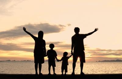 Familia en la playa saludando.