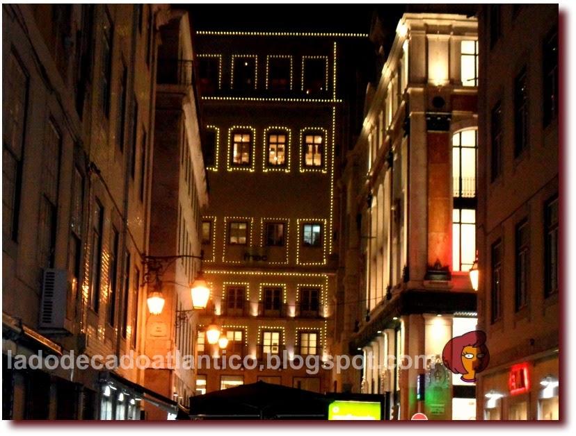 Foto das janelas iluminadas das lojas do Armazém do Chiado vistas da Rua da Assunção, em Lisboa