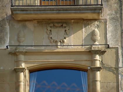 Detall de la façana principal del mas Barnils de finals del segle XIX, datada al 1887 i amb un escut centrat al seu damunt