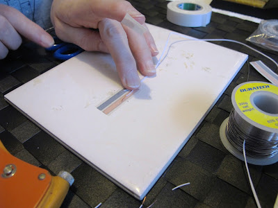 Woman about to stick down a length of wire onto a run of copper tape to a tile.