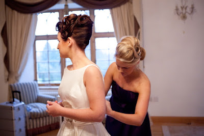 Bridesmaids in blue dresses getting ready at a wedding with bride