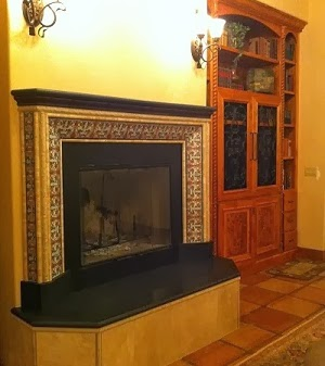 e right at home with the terracotta floor pavers, stone molding and black granite mantle and bench.