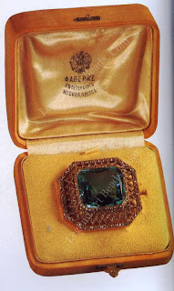 Right, aquamarine brooch pendant in a broad red gold trellised frame set with brilliant and rose diamonds following the canted contour of the stone. Fitted in its original holly box.