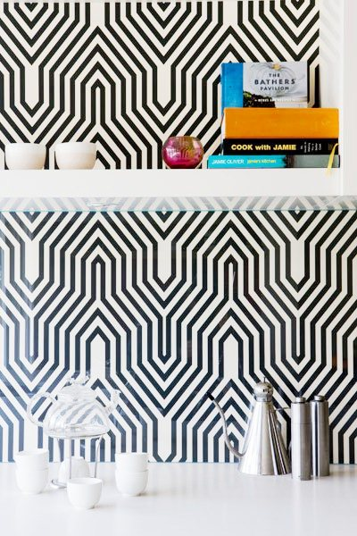 close up of kitchen with black and white geometric backsplash and white floating shelves