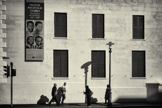 People on Bureau Street in Cape Town beneath a poster advertising an exhibition of Oliver Tambo's life.