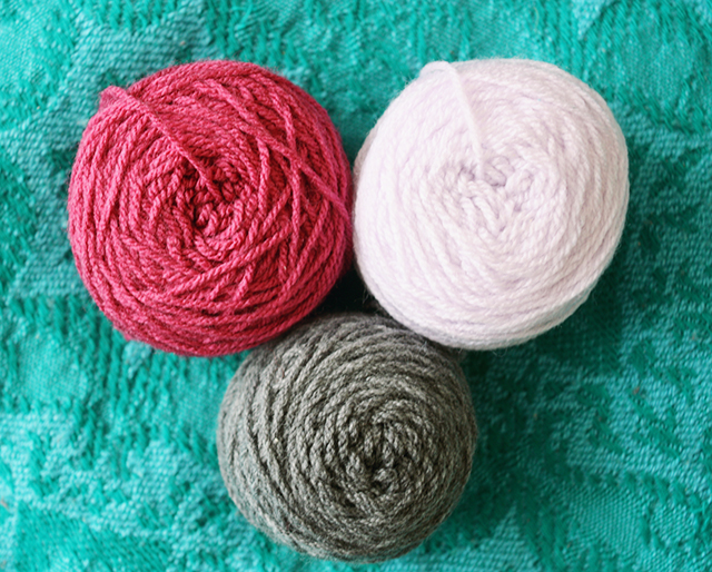 balls of wool in pink, lilac and grey on a turquoise blanket