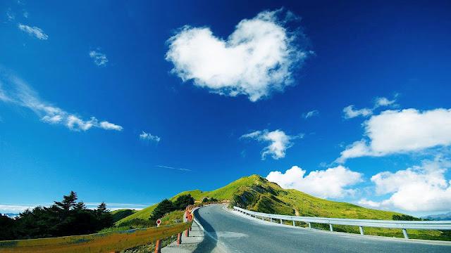Foto van een heuvel met weg en een wolk in de vorm van een hartje