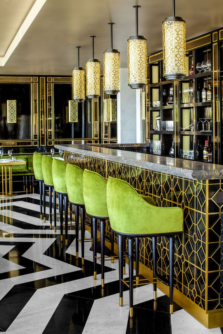 Marble bar with brass accents and green barstools