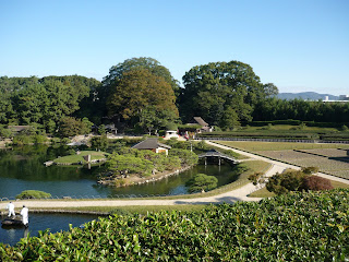 Korakuen Garden (Okayama) as seen from hill in the middle, there's the main bond with a bridge and islands, a smaller pond being cleaned by two workers dressed in white and a cultivated field next to the pond.