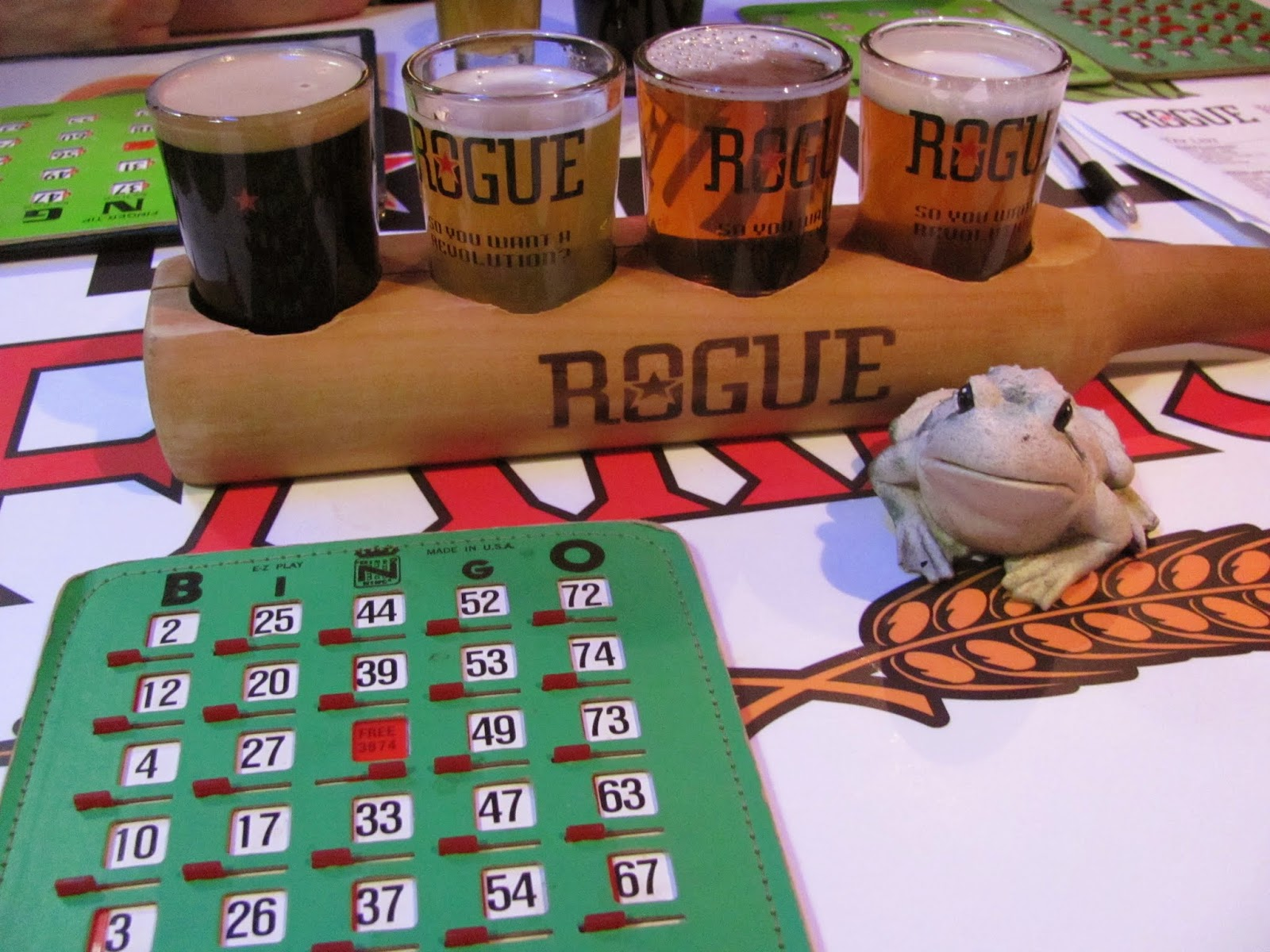 Frog poses with Bingo cards and the flight of beverages at Rogue Brewing in Eugene, Oregon