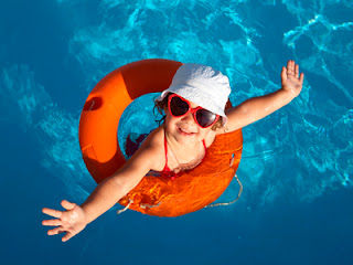 little girl with lifesaver in swimming pool