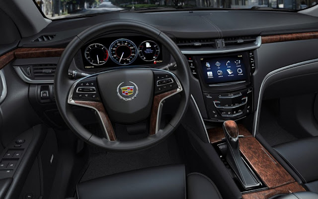 2013 Cadillac XTS interior, black with wood accents, CUE touchscreen and reconfigurable gauge cluster