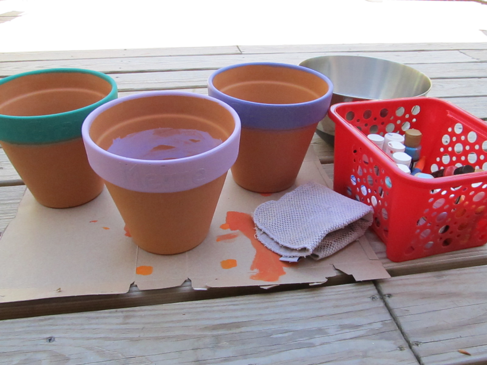 Again using craft acrylic paint we painted Big Brother's hands and made  prints on the sides of the pots. We set up a bowl of soapy, warm water and  rags for ...
