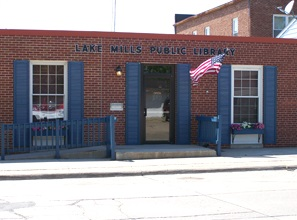 Picture shows a one-story brick building with two large windows on either side of a door. Windows and door are framed with blue shutters. An American flag flies on a pole in front. Lake Mills Public Library is written over the door in blue block letters.