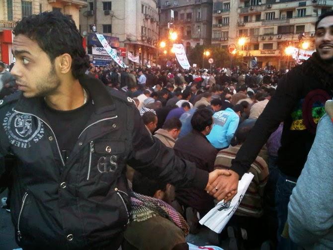 Христиане защищают мусульман, пока те молятся во время революции в Каире, Египет, 2012 год.