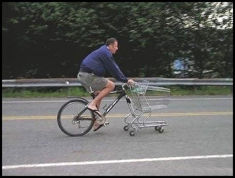 Hombre en una bicicleta, con un carrito de la compra por rueda delantera.