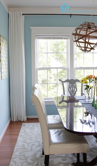 dining room with white curtains, white parson chairs and pedestal table