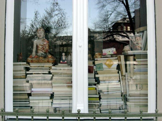 Bücher stapeln sich in einem Fenster, oben drauf sitzt eine Buddha-Figur