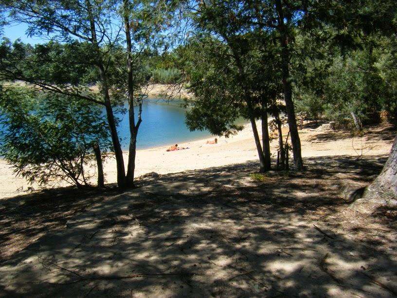 Sombra e gente na praia fluvial a apanhar sol