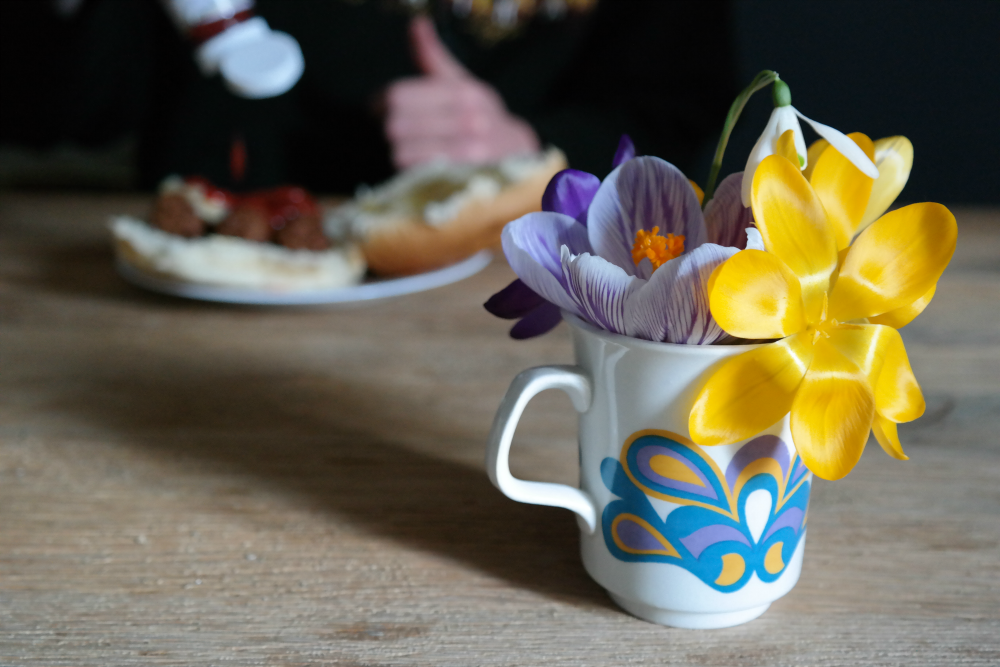 Crocuses in a Meakin cup. Steve pouring ketchup on a sausage sandwich in the background.
