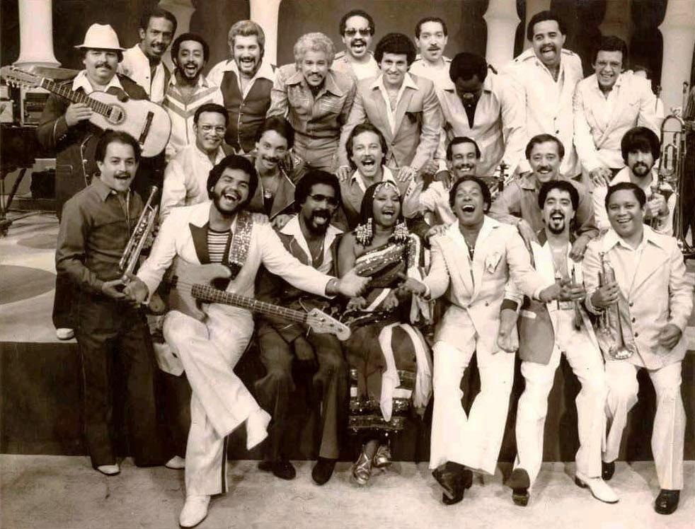"""La Fania All Stars en una fotografía de 1980. """"Cheo"""" Feliciano está sentado en primera fila, al lado de la cantante cubana Celia Cruz"""