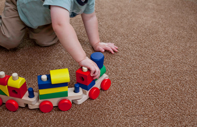 child plays on comfortable carpet