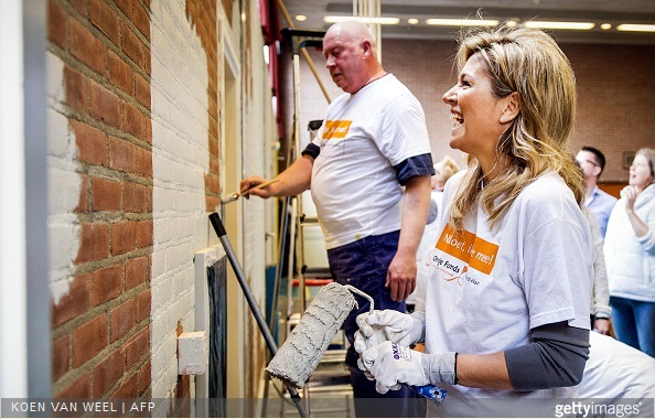 Dutch Queen Maxima laughs as she paints a wall in the sports area of a cultural centre in the village Tricht, on March 21, 2015. Members of the Dutch royal family take part in the national voluntary event NLdoet.