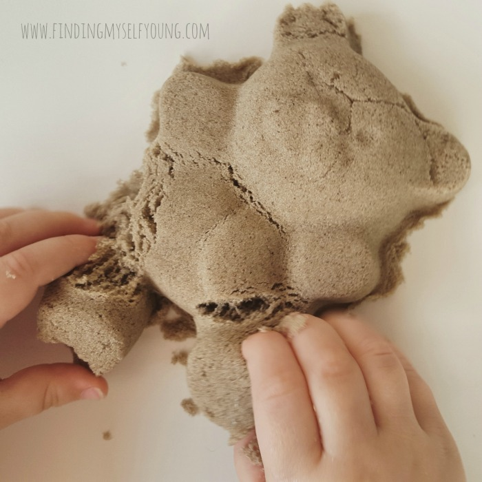 toddler fingers playing with kinetic sand teddy bear mould