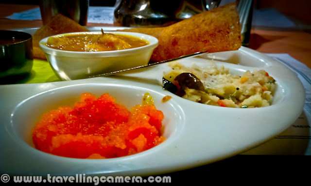 Few days back one of my friend told me about Sarvana Bhavan in Connaught place and we though of having lunch at the same place. It's just opposite to Janpath Market near CP, Delhi. Let's have a quick Photo Journey to Sarvana Bhavan in Connaught Place with some information about it's food and specialties...Welcome to Sarvana Bhavan. As you know, all popular places in Delhi are usually crowded. So the story of our lunch also started with waiting time for 25 minutes. And after a long wait we had to share the table. Since my friend was crazy about the South Indian food here, I simply followed the trends if Sarvana Bhavan. Otherwise I would have spent those 25 mins in locating some other good place which could offer comfortable seating at least.Here is what exactly we saw inside Sarvana Bhavan. Both of the floors were full of people and seating were extremely tight. There was hardly any space between the tables. It seemed that they get lot of customers daily and available real-estate need to be utilized in such a way.Place is fine for young and old age folks, but if someone want to visit the place with children, I would want to warn them. Waiting for 20 minutes at least and then getting into a tight space and get out of the space after finishing your food - This whole cycle will suffocate the kids with you. As there is no place for them to enjoy inside Sarvana Bhavan.Anyway, it was time to look at the menu and decide on items we wanted to have for Lunch. I got the reasoning behind the popularity and spacing problem. Their charges were very nominal. But I was expecting lovely south Indian food at same time. Let's see how it goes...We were sharing our table with this interesting couple, who ordered very unique items in lunch. They took enough time to look at all the items in Menu and then decided to have a special thali and Paper masala Dosa, with salted Dahi-Vada after main meal.Overall place was clean and comfortable, if we forget about the spacing. It's a completely air