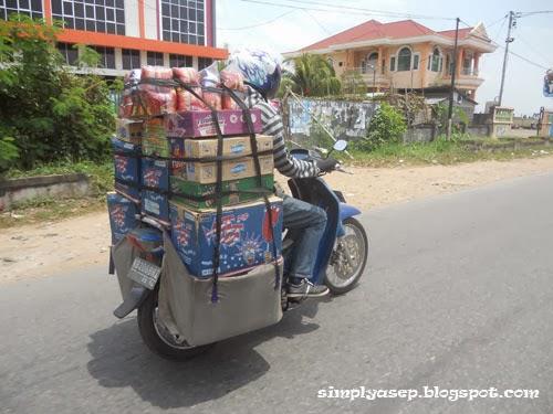 Pengendara motor dengan bawaannya. Berat dan berbahaya. Foto Asep Haryono