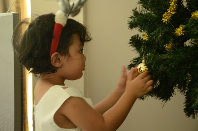 Kecil putting up baubles on the Christmas tree