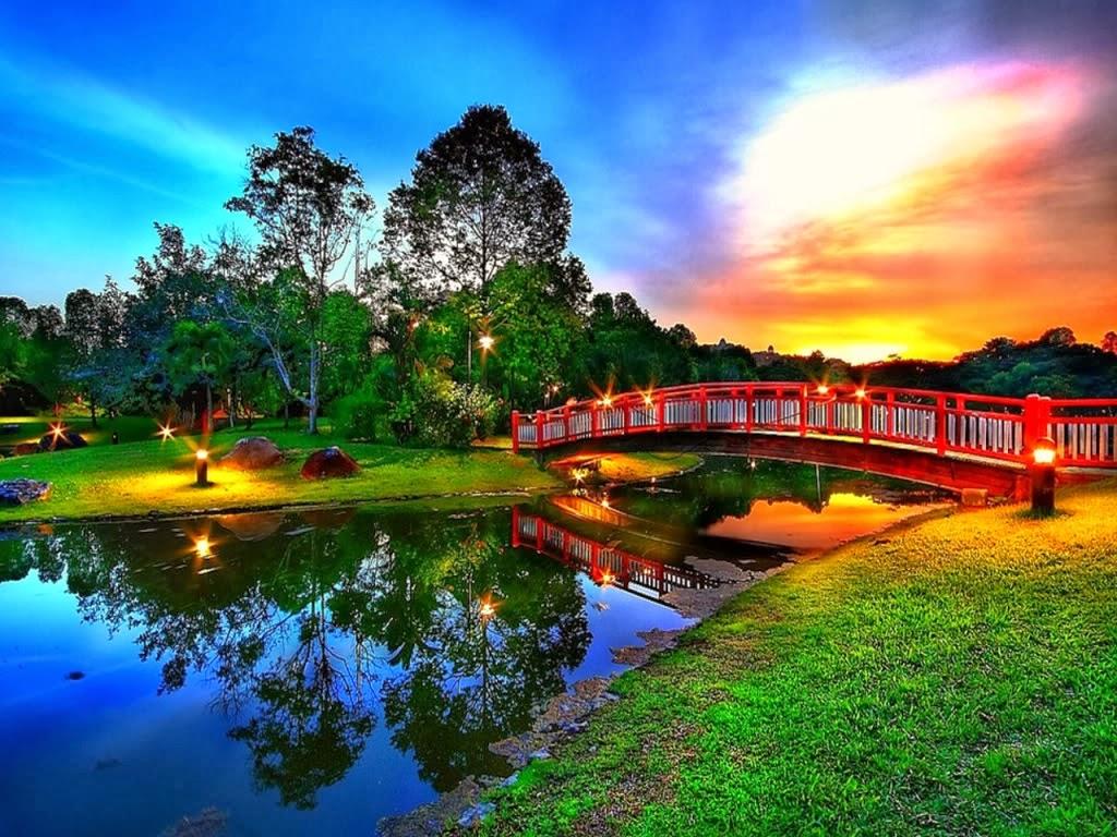 Jardín rodeando un lago que tiene como puente uno rojo.