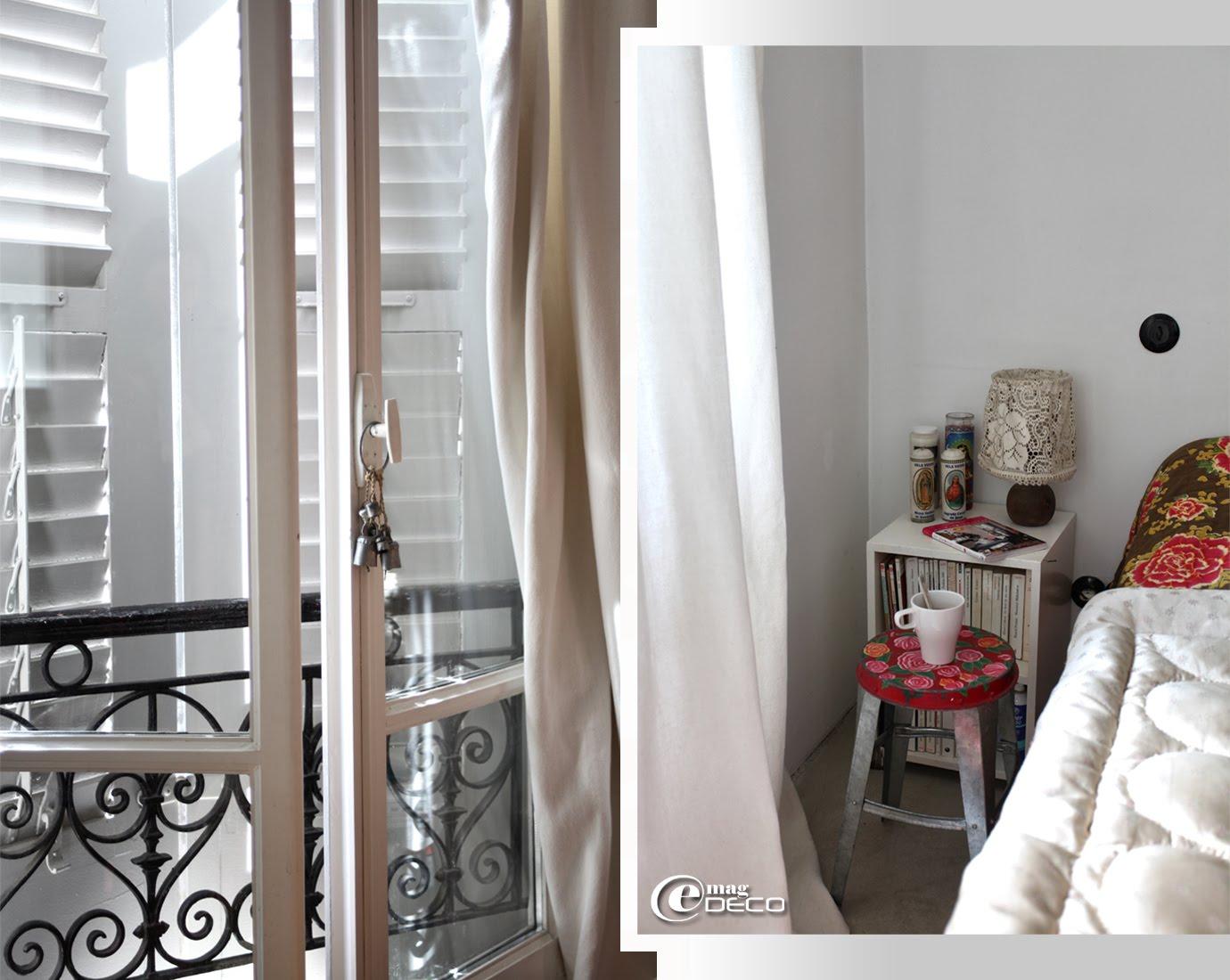 Derrière une fenêtre, des volets persiennes à lames articulées
