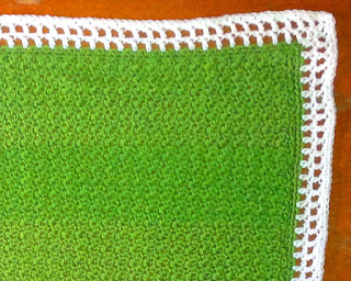 Green blanket crocheted in griddle stitch with a white filet-style crocheted border.