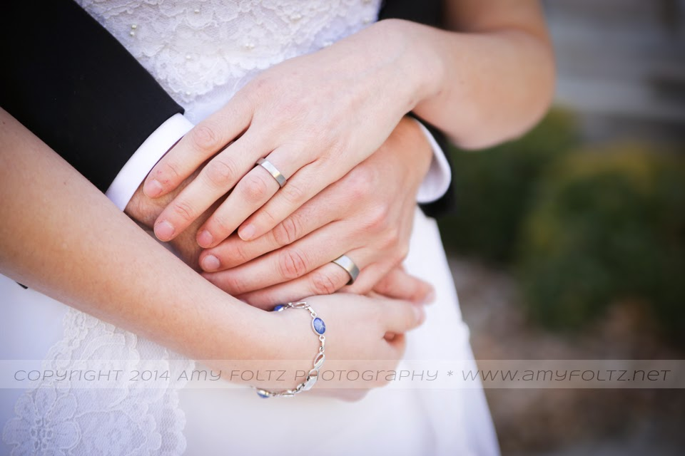 photo of bride and groom's hands with wedding rings