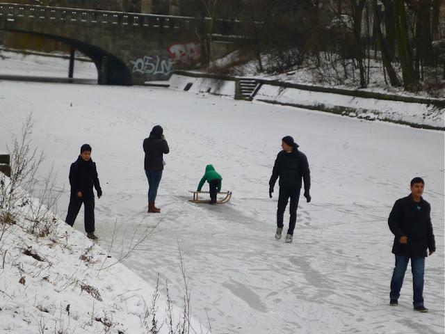 Auf dem Eis: Drei Männer, eine Frau und ein Kind mit Schlitten, die dunklen Figuren zeichnen sich vor dem Eis des zugefrorenen Landwehrkanals fast scherenschnittartig ab.